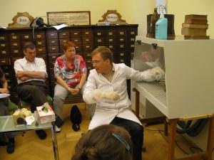 Markus Bürscher demonstriert den gespannten TeilnehmerInnen, wie ein von Schimmel befallenes Buch in einer mobilen Absauganlage gereinigt wird.